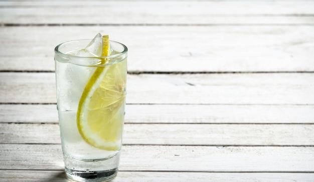 Colpi di vodka con limone e ghiaccio. su un tavolo di legno bianco.