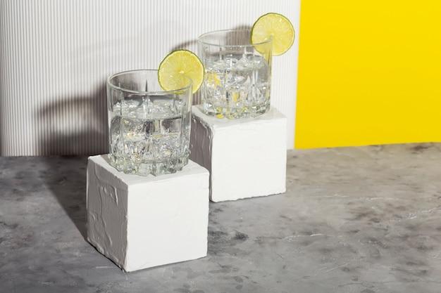 Vodka con ghiaccio e lime in due bicchieri su supporto bianco