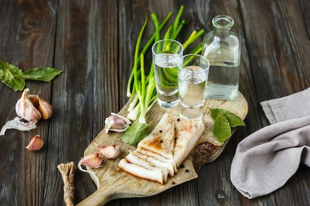 Vodka con lardo e cipolla verde sulla parete in legno. bevanda alcolica pura artigianale e snack tradizionali. spazio negativo. celebrando il cibo e delizioso.