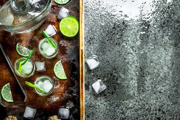 Vodka con lime e ghiaccio su un vassoio di legno. su fondo rustico.