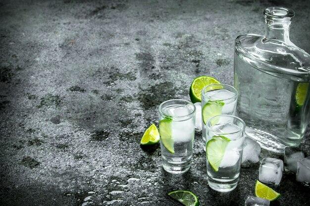 Vodka con pezzi di lime e cubetti di ghiaccio. su fondo rustico