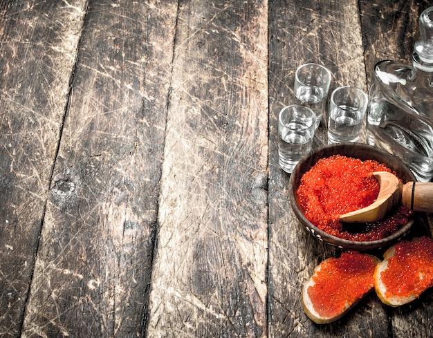 Vodka con caviale rosso. sullo sfondo di legno.