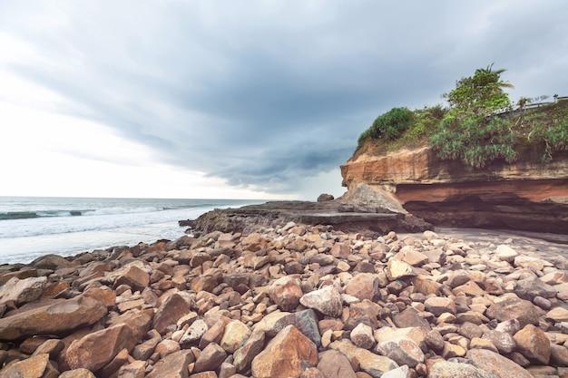 Spiaggia vulcanica con montagne rocciose a bali, indonesia