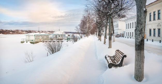 L'argine del fiume volga a plyos nella neve, una panchina e moli innevati alla luce di una giornata invernale