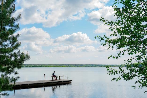 Fiume volga, russia, 28 maggio 2021. un ragazzo con una canna da pesca sta pescando nel fiume in estate.