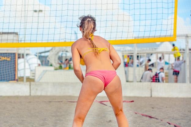 Il giocatore di beach volley è un giocatore di pallavolo atleta femminile che si prepara a servire la palla sulla spiaggia.