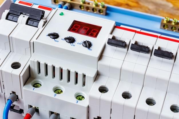 Limitatore di tensione e primo piano degli interruttori automatici nella scatola di montaggio in plastica bianca