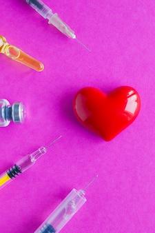 Cuore volumetrico con siringhe su una superficie rosa. il concetto di supportare i pazienti con malattie cardiache
