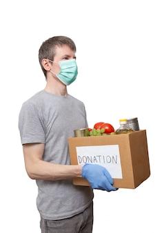 Volontario in guanti protettivi blu che tengono l'alimento della drogheria in scatola di donazione del cartone
