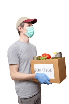 Volontario in guanti protettivi blu che mostrano l'alimento della drogheria in scatola di donazione del cartone