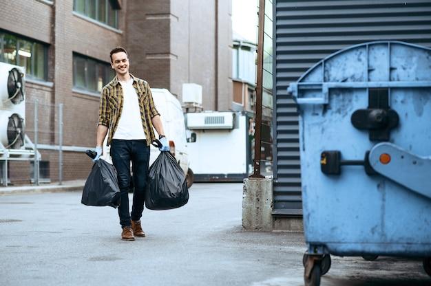 Il volontario trasporta i sacchetti della spazzatura di plastica alla lattina all'aperto, facendo volontariato. la gente pulisce le strade della città, il restauro ecologico, la raccolta e il riciclaggio dei rifiuti, la cura dell'ecologia, la pulizia dell'ambiente