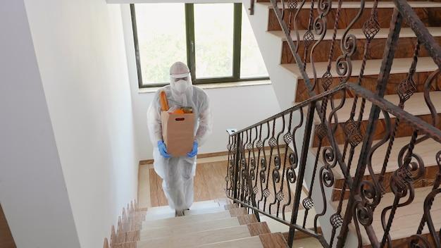 Volontariato che consegna ordini di cibo indossando una tuta nella pandemia di covid-19.