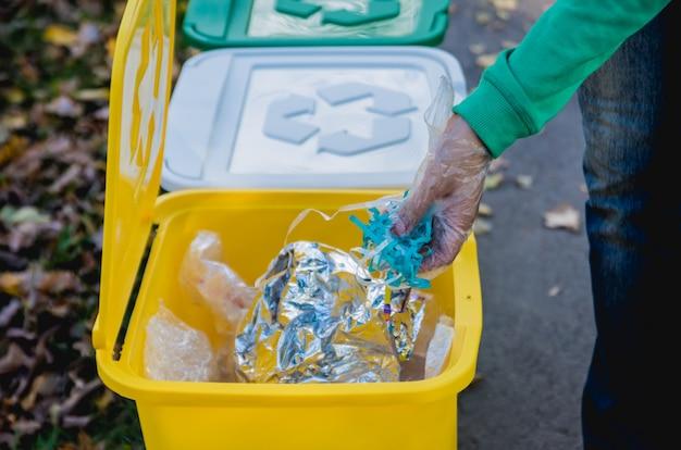 La ragazza volontaria ordina la spazzatura nella via del parco. concetto di riciclaggio.