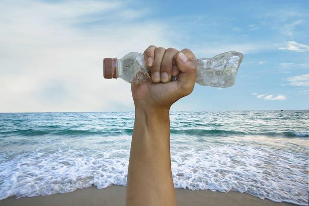 La mano volontaria afferra una bottiglia di plastica con l'onda del mare sullo sfondo