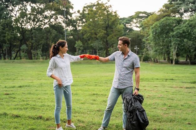Coppia di amanti volontari che indossano guanti che camminano per raccogliere la spazzatura nel parco per mantenere l'ambiente pulito