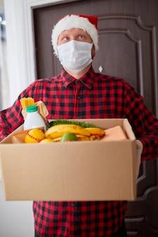 Uomo volontario con cappello da babbo natale e maschera protettiva e guanti consegna scatola di donazione a casa nelle vacanze di natale corriere con scatola di imballaggio con consegna senza contatto alimentare servizio quarantena coronavirus