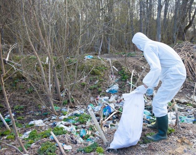 Un uomo volontario in abiti protettivi bianchi raccoglie la spazzatura
