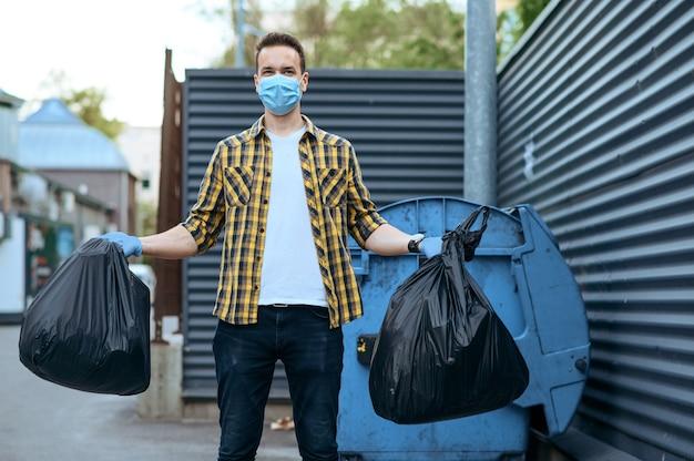 Volontario in maschera tiene sacchetti di plastica della spazzatura all'aperto, volontariato. la gente pulisce le strade della città, il restauro ecologico, la raccolta e il riciclaggio dei rifiuti, la cura dell'ecologia, la pulizia dell'ambiente