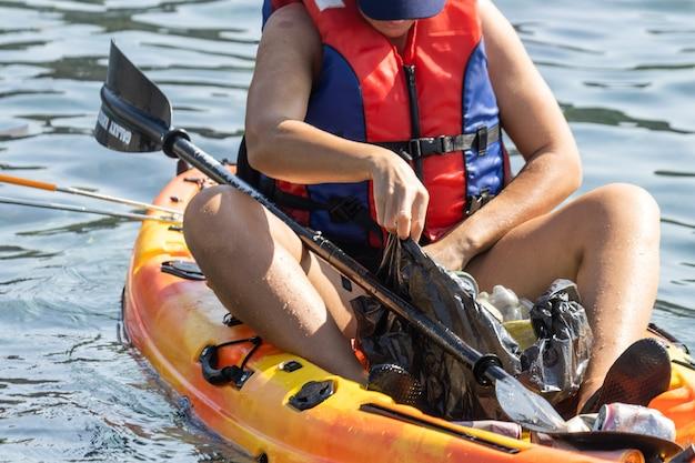 Persona volontaria in kayak che raccoglie rifiuti e plastica nell'oceano