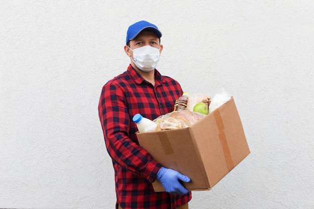 Il volontario in una maschera protettiva con una scatola di cibo, donazione