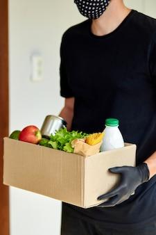 Volontario nella scatola di donazione per la consegna di guanti e maschera medica protettiva a casa