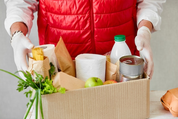 Volontario nella maschera protettiva medica e guanti che mettono cibo nella scatola di donazione.