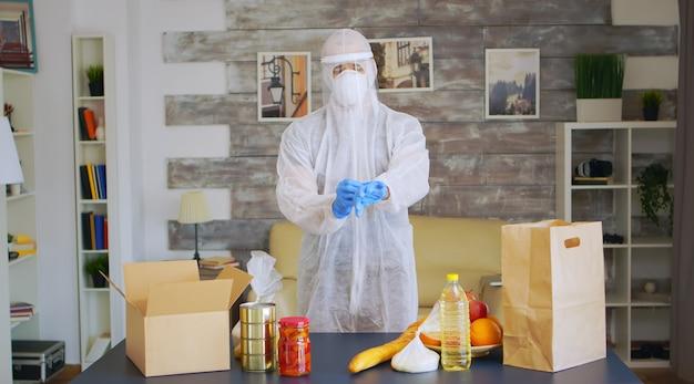 Volontariato in tuta protettiva con guanti che imballano cibo durante il coronavirus.