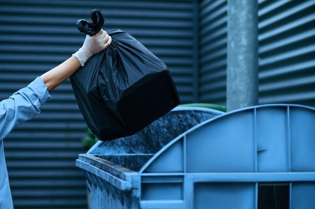 Il volontario mette il sacco della spazzatura di plastica nel cestino all'aperto, offrendosi volontario. la gente pulisce le strade della città, il restauro ecologico, la raccolta e il riciclaggio dei rifiuti, la cura dell'ecologia, la pulizia dell'ambiente