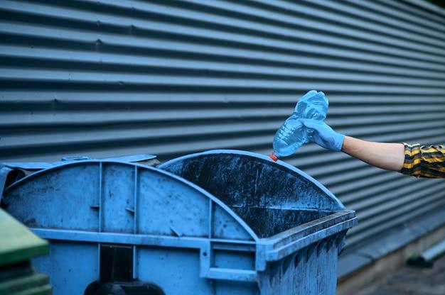 Il volontario mette la spazzatura nella lattina all'aperto, facendo volontariato