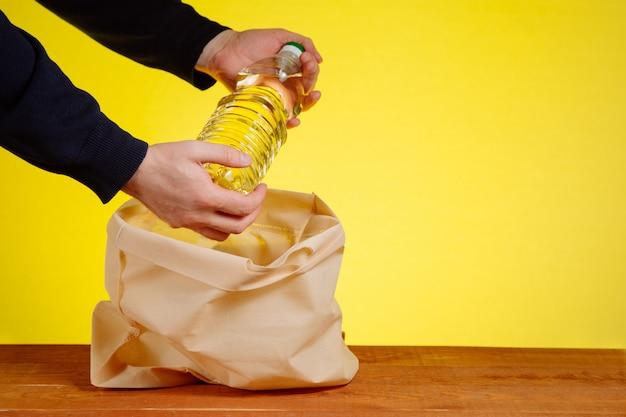 Le mani del volontario hanno messo una bottiglia di olio vegetale in un sacchetto per le donazioni.