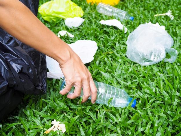 Spirito di volontariato con la conservazione e la salvaguardia dell'ambiente tramite la raccolta dei rifiuti bottiglia di acqua in plastica con sacchetto nero scaricata nella spazzatura gialla da riciclare.
