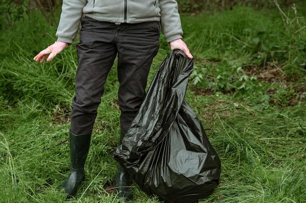 Volontariato con un sacco della spazzatura in un viaggio nella natura, pulendo l'ambiente.