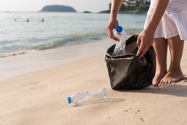 Donna volontaria che raccoglie immondizia sulla spiaggia. concetto di ecologia