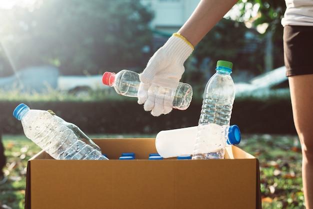 La donna volontaria tiene la bottiglia di plastica nella scatola di carta al parco pubblico, smaltisce il concetto di riciclo e gestione dei rifiuti, buona mente cosciente