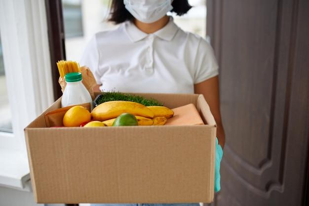 Donna volontaria in maschera protettiva bianca e guanti consegna scatola di donazione a casa, corriere con scatola di imballaggio con cibo, consegna senza contatto
