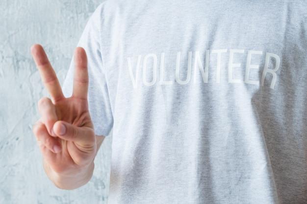 Attività di volontariato. concetto di stile di vita moderno. uomo in maglietta che mostra il segno v.