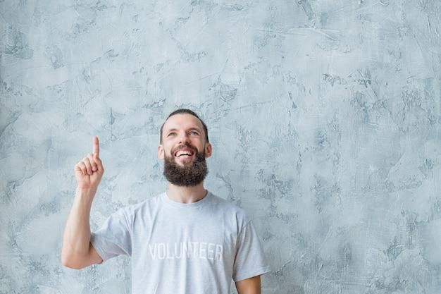 Attività di volontariato. concetto di stile di vita moderno. uomo in maglietta con il dito indice in alto.