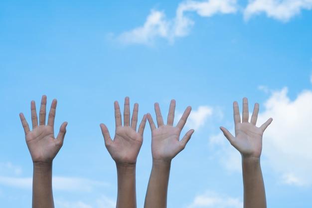 Concetto di volontariato. mani di persone con cielo blu su sfondo