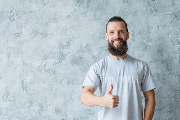 Concetto di volontariato. stile di vita responsabile. giovane uomo barbuto sorridente con il pollice in su.