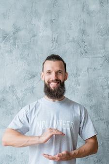 Stile di vita di volontariato. concetto di giornata della terra. uomo sorridente che tiene globo immaginario. Foto Premium
