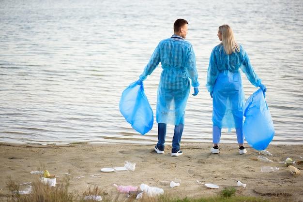 Volontari che raccolgono bottiglie di plastica nel sacco della spazzatura, ecologia, natura, inquinamento, spazzatura, cura, volontariato di beneficenza, ambiente comunitario.
