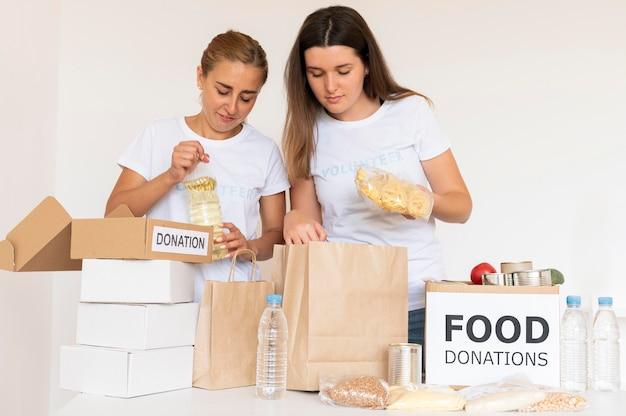Volontari che ricevono cibo in sacchetti per la donazione