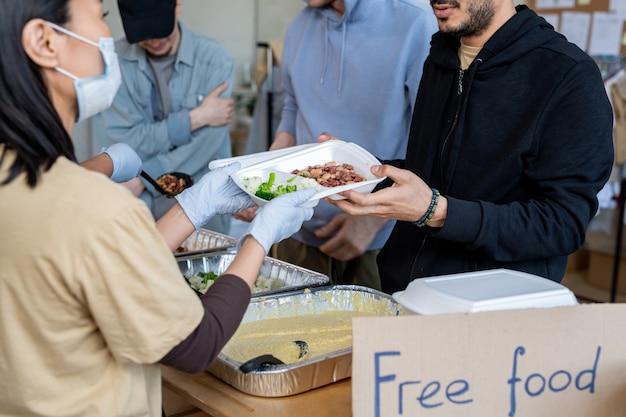 Volontari con guanti e mascherine che servono cibo gratis a rifugiati o senzatetto