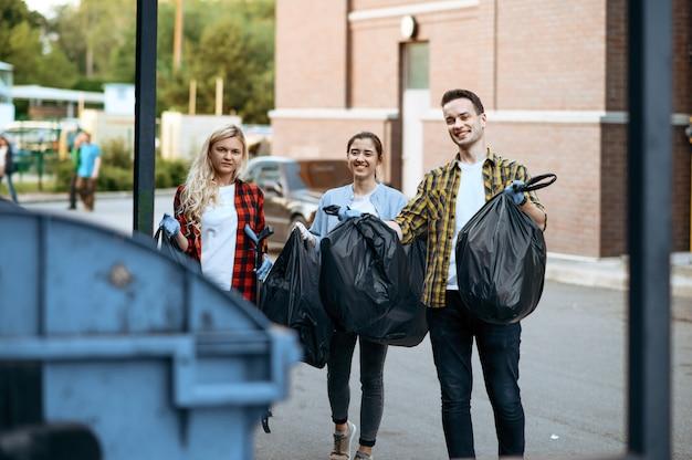 I volontari tengono i sacchetti di plastica della spazzatura all'aperto, facendo volontariato. la gente pulisce le strade della città, il restauro ecologico, lo stile di vita ecologico, la raccolta e il riciclaggio dei rifiuti, la cura dell'ecologia, la pulizia dell'ambiente