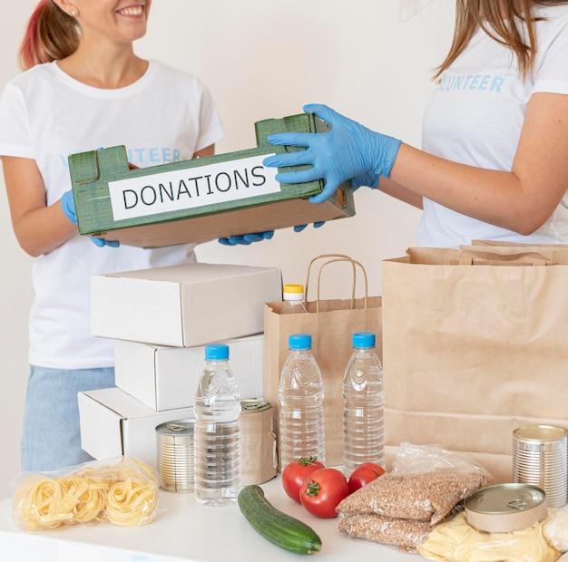 Volontari che preparano scatole di donazioni di cibo