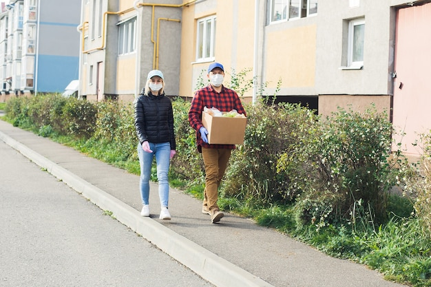 Volontari con maschere protettive camminano per strada con una scatola di generi alimentari, beneficenza.