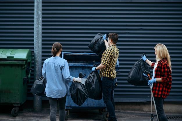 I volontari mettono i sacchetti della spazzatura di plastica nella lattina all'aperto, facendo volontariato. la gente pulisce le strade della città, il restauro ecologico, la raccolta e il riciclaggio dei rifiuti, la cura dell'ecologia, la pulizia dell'ambiente