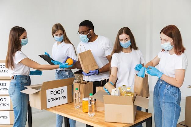 Volontari con guanti e maschere mediche che preparano il cibo per la donazione