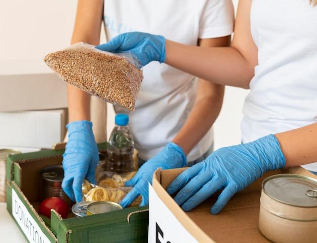 Volontari con guanti che preparano scatole di donazioni di cibo