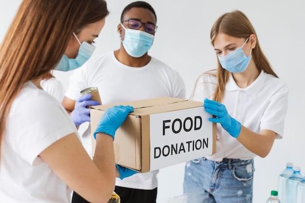 Volontari con maschere mediche che preparano scatole per le donazioni